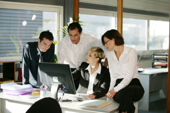 In an office, four employees discuss the business situation in front of a PC.