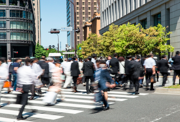 A group of people cross a pedestrian crossing
