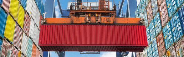 Red container seen from below being moved by a crane