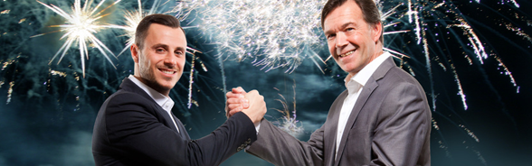 Two men in suits shaking hands in front of a fireworks display