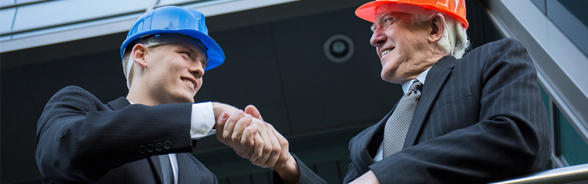 Two smiling men in suits, wearing hard hats, shaking hands