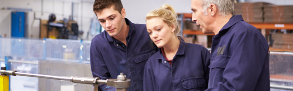 Two apprentices in work clothes listening to an instructor's advice